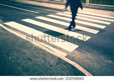 Vintage and grunge blurry road crossing with pedestrian feet. Vintage and grunge filter effect used. - stock photo