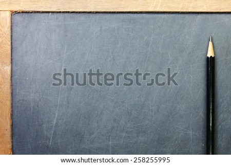 Vintage and old slate blackboard and wooden pencil put on the black color leather background represent the teaching equipment related. - stock photo
