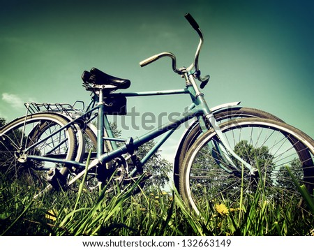 Vintage and Toned Photo of Two Vintage Bicycles on the Summer Meadow - stock photo
