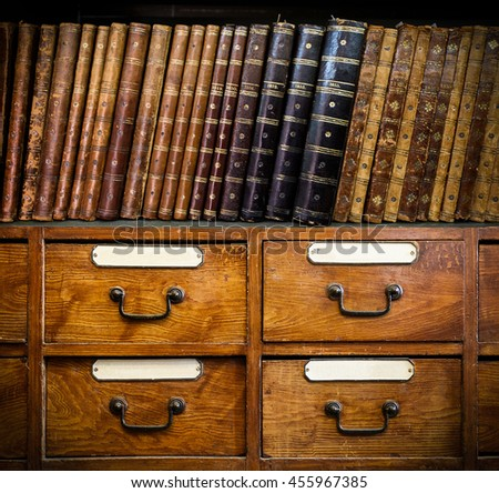 Vintage, antiquarian books on wooden cabinet. Retro background. - stock photo