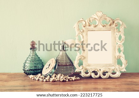 vintage antique perfume bottles with old picture frame, on wooden table. retro filtered image - stock photo