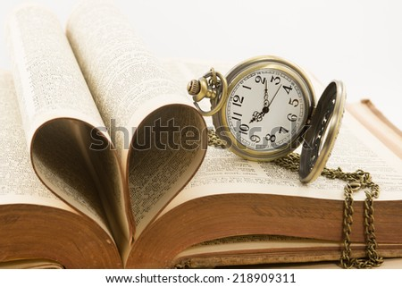 Vintage antique pocket watch and heart of the book's pages - stock photo