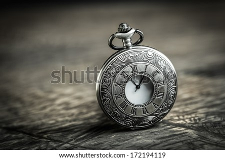 Vintage Antique pocket watch on grunge wooden background - stock photo
