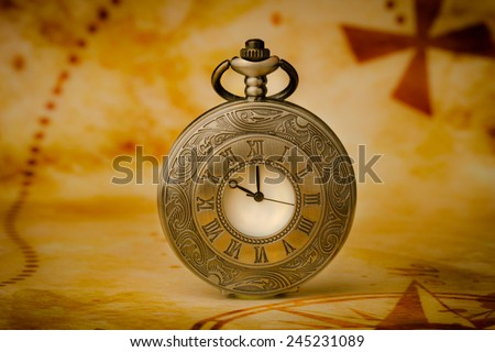 Vintage antique pocket watch on old map background - stock photo