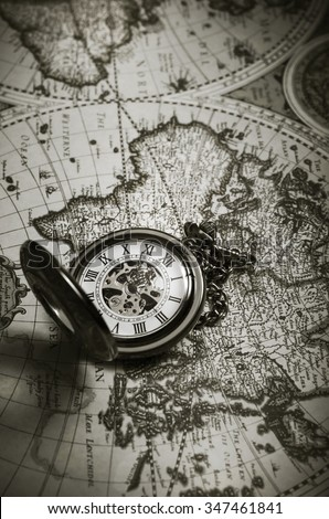 Vintage antique pocket watch on old map background, close up - stock photo