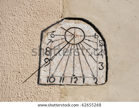 Vintage Antique Sun Dial on Cement Building Wall - stock photo