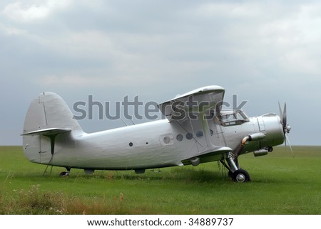 Vintage Antonov plane from last century. Standing on the grass field.