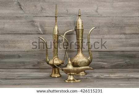 Vintage arabic jug, vase, lamp, teapot. Golden oriental decorations on wooden background - stock photo