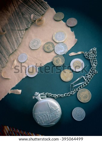 Vintage arabic silver pocket watch surrounded with the arabic coins at the black background. - stock photo