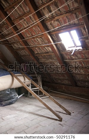 Vintage attic - roof frame, ladder and junk - stock photo