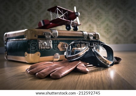 Vintage aviator equipment on the floor with glasses, gloves and toy plane. - stock photo
