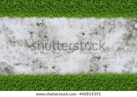 Vintage background of green grass frame and concrete wall texture. - stock photo