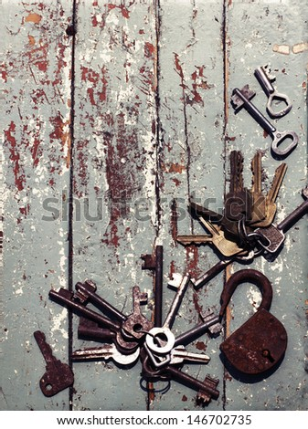 vintage background with locks and lots of keys on wooden table with grunge texture - stock photo