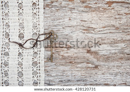 Vintage background with old key and lace on the rude weathered wood
