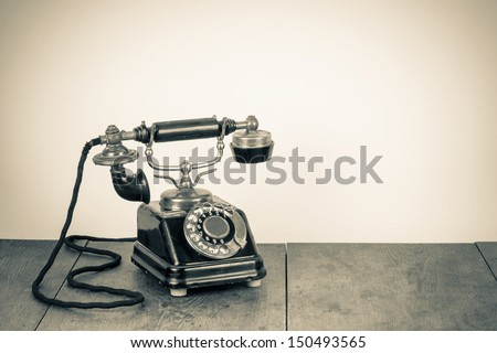 Vintage background with old rotary telephone on wood table - stock photo