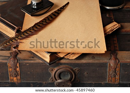 Vintage background with old scrapbook and writing supplies on rustic steamer trunk.   Copy space on yellowed pages of scrapbook. - stock photo