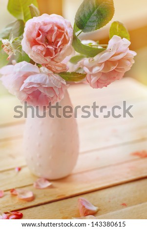Vintage background with Pink flowers in a vase/ pink roses on light wooden table