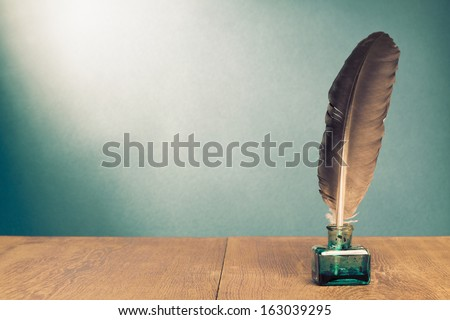 Vintage background with quill pen, inkwell on wooden table - stock photo