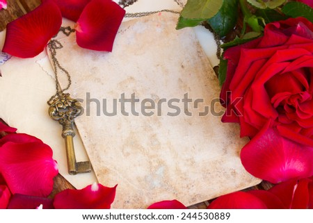 vintage background with red rose petals and antique skeleton key - stock photo