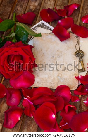 vintage background with red rose petals on wooden table - stock photo