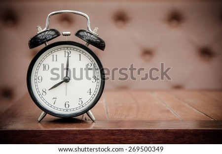 Vintage background with retro alarm clock on table upholstery leather pattern background - stock photo