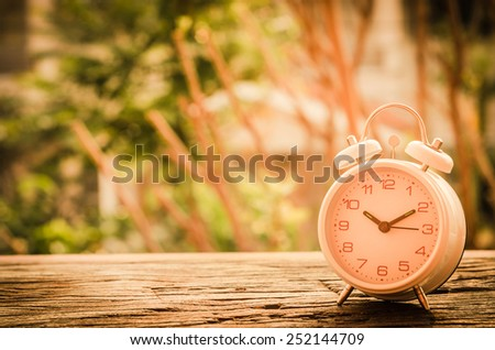 Vintage background with retro alarm clock on wooden table. black and white - stock photo