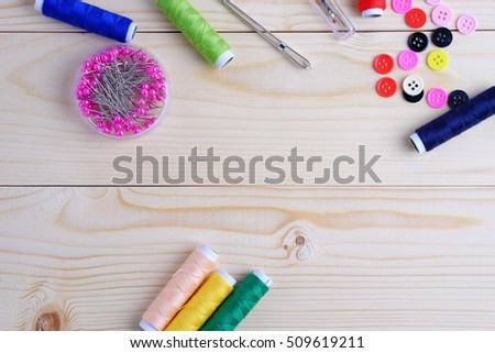 Vintage background with sewing kit and accessories for needlework on wooden background. Blank space and top view concept.