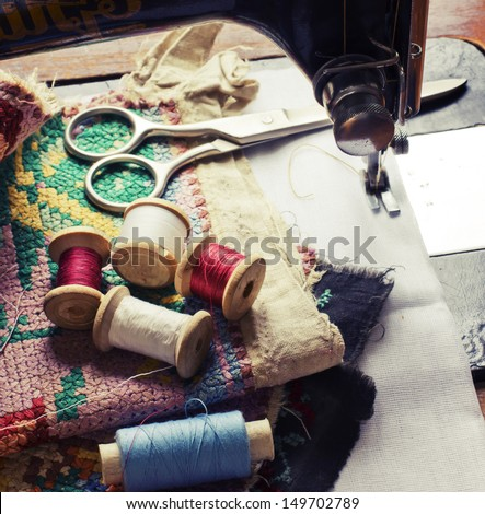 Vintage Background with sewing/Sewing kit. Scissors, bobbins with thread and needles on the old wooden background - stock photo