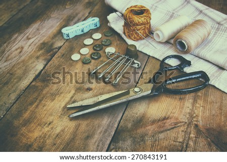 Vintage Background with sewing tools and sewing kit over wooden textured background low ket image with retro faded style - stock photo