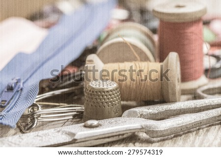 Vintage background with sewing tools and sewing kit. Scissors, bobbins, buttons on the old wooden background. Old style, sepia - stock photo