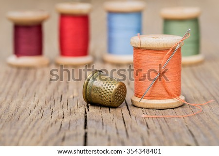 Vintage background with sewing tools and sewing kit. Scissors, bobbins, buttons on the old wooden background. - stock photo