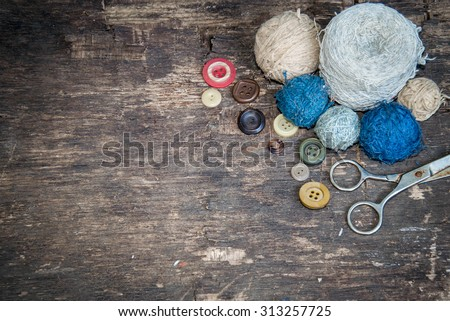 Vintage background with sewing tools. Old scissors, buttons and balls of yarn on the old wooden background.   - stock photo