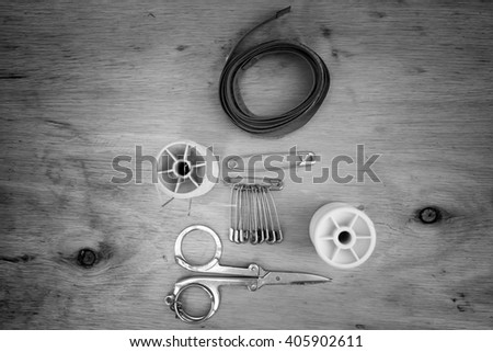 Vintage Background with sewing tools/Sewing kit. Scissors, bobbins with thread and needles on the old wooden background - stock photo