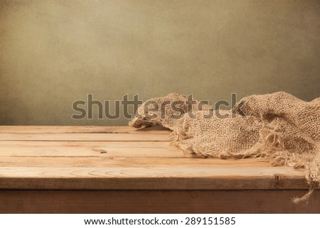 Vintage background with wooden table and sackcloth - stock photo