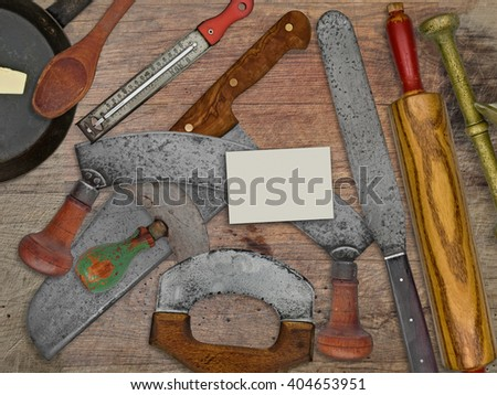 vintage bakery shop tools and utensils over stained wooden table, blank business card for your text - stock photo