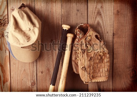 Vintage baseball equipment still life. A glove, two bats and hats against a rustic wooden wall. Horizontal format - stock photo