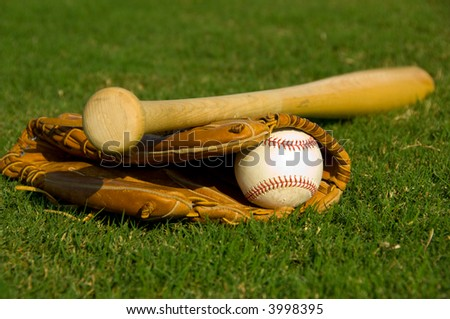 Vintage baseball with bat and glove on grass field