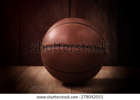 Vintage basketball on a wooden court background in the spotlight - stock photo