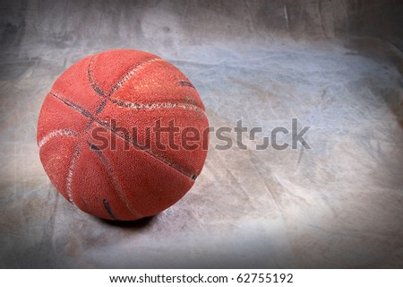 Vintage basketball on brown back drop with copy space ball is very cracked and aged with texture - stock photo