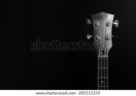 vintage bass guitar headstock on a black background - stock photo