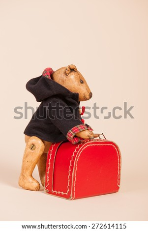 Vintage bear with coat and suitecase on beige background - stock photo