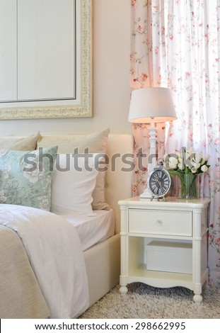 vintage bedroom interior with decorative table lamp, alarm clock and flower on white table - stock photo