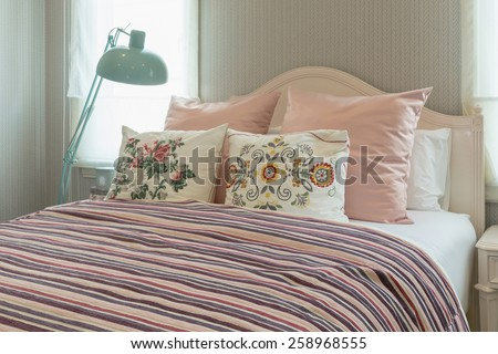 vintage bedroom interior with flower pillows and pink striped blanket on bed - stock photo