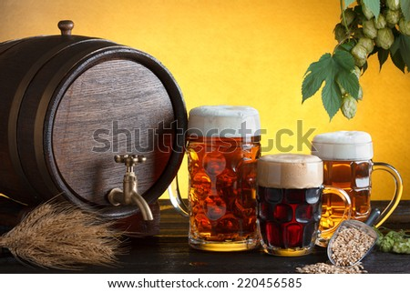 Vintage beer barrel with beer glasses on wooden table with wheat bunch, hop and barley, still life with copy space - stock photo
