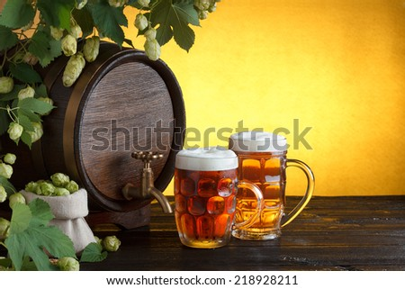 Vintage beer barrel with two beer glasses and frame of fresh hops on wooden table still life, copy space