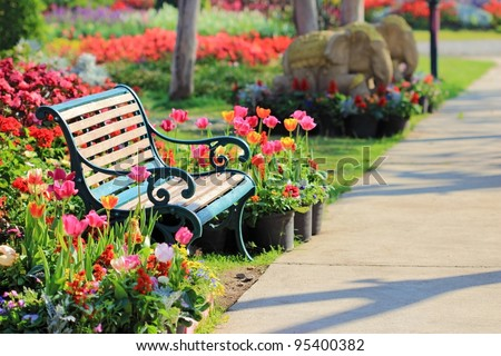Vintage Bench in tulips garden - stock photo