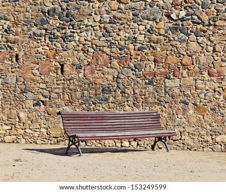 vintage bench near stone wall - stock photo
