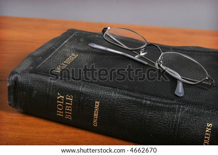 Vintage Bible and eyeglasses on wooden table.