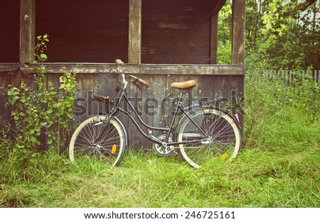 vintage bicycle at old wooden, desolate house in the forest