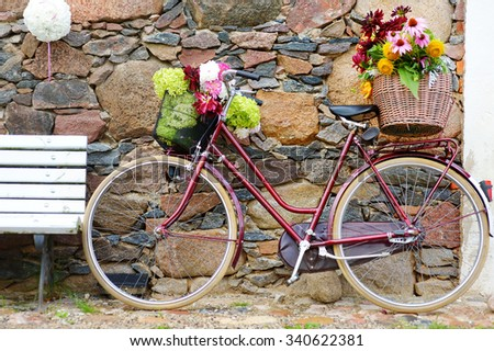 Vintage bicycle decorated with various flowers - stock photo